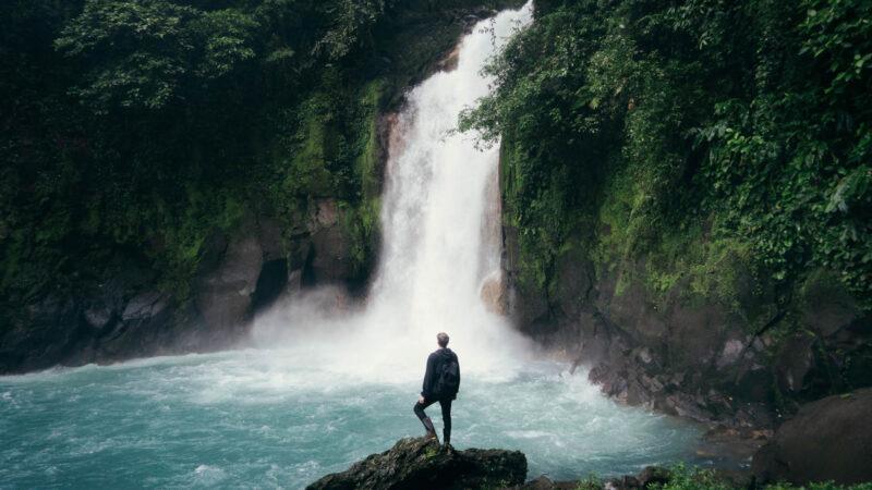Hombre frente a una catarata en Costa Rica