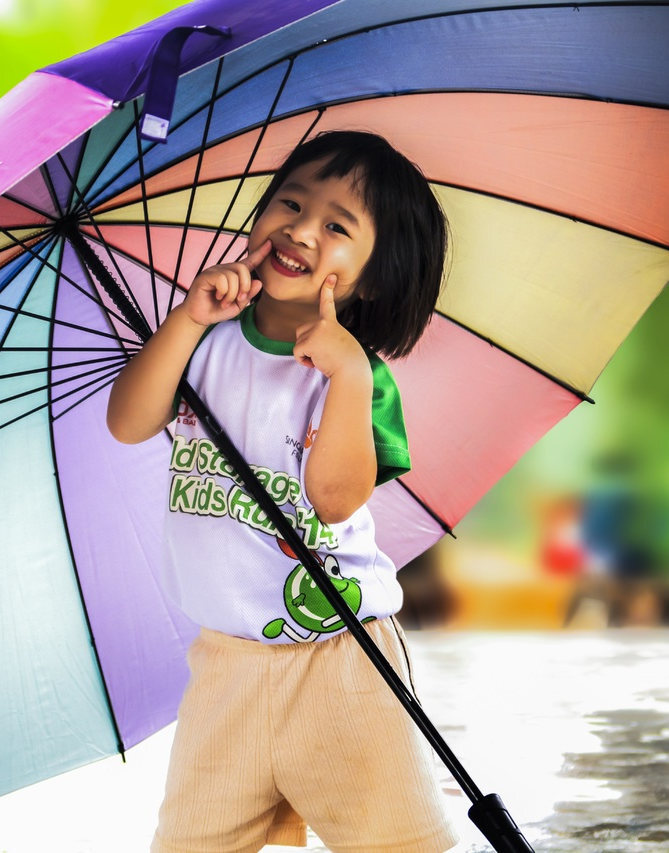 a kid playing in the rain with an umbrella